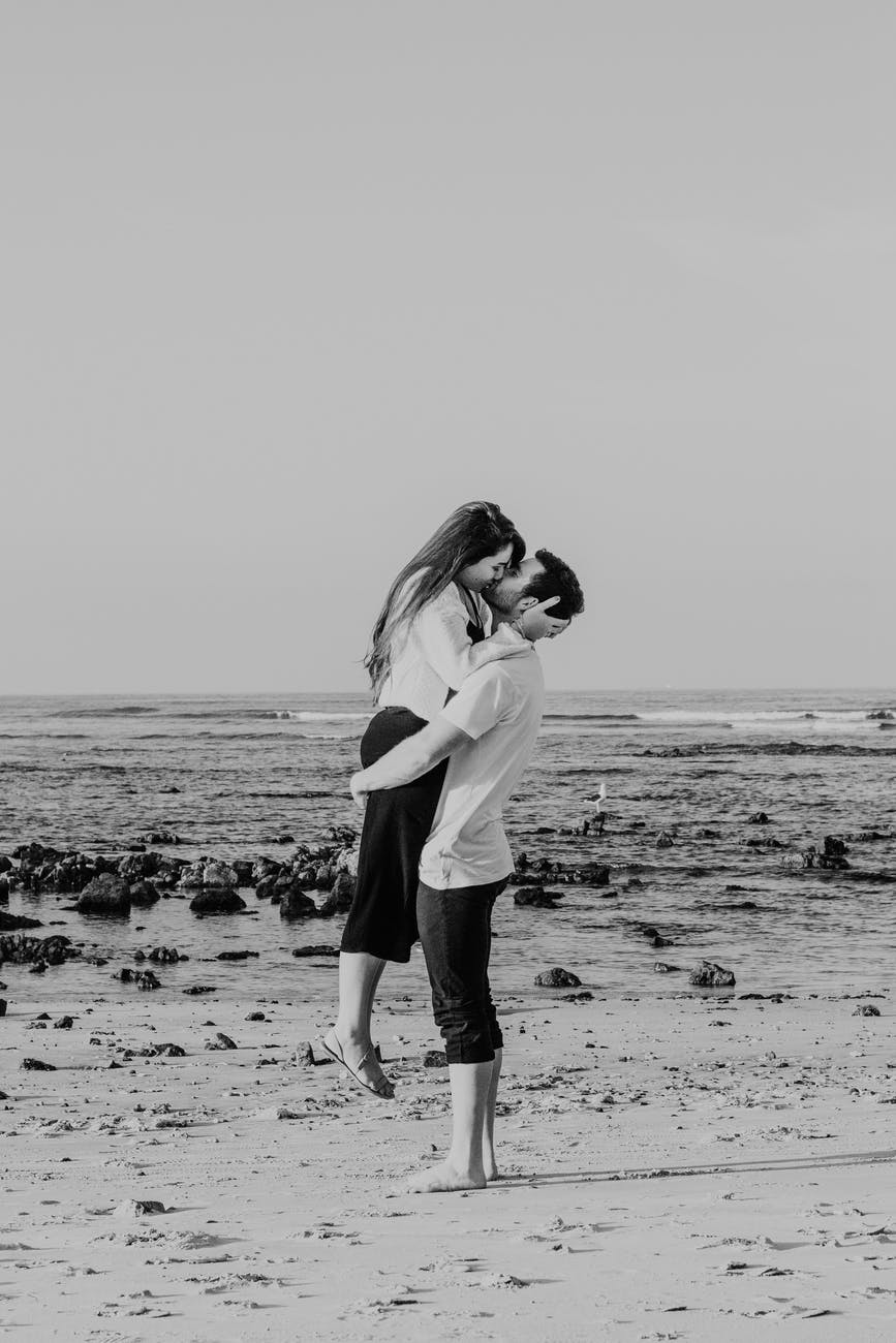 loving couple embracing and kissing passionately on seacoast