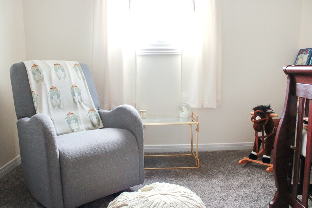 Glider chair and end table by window in nursery