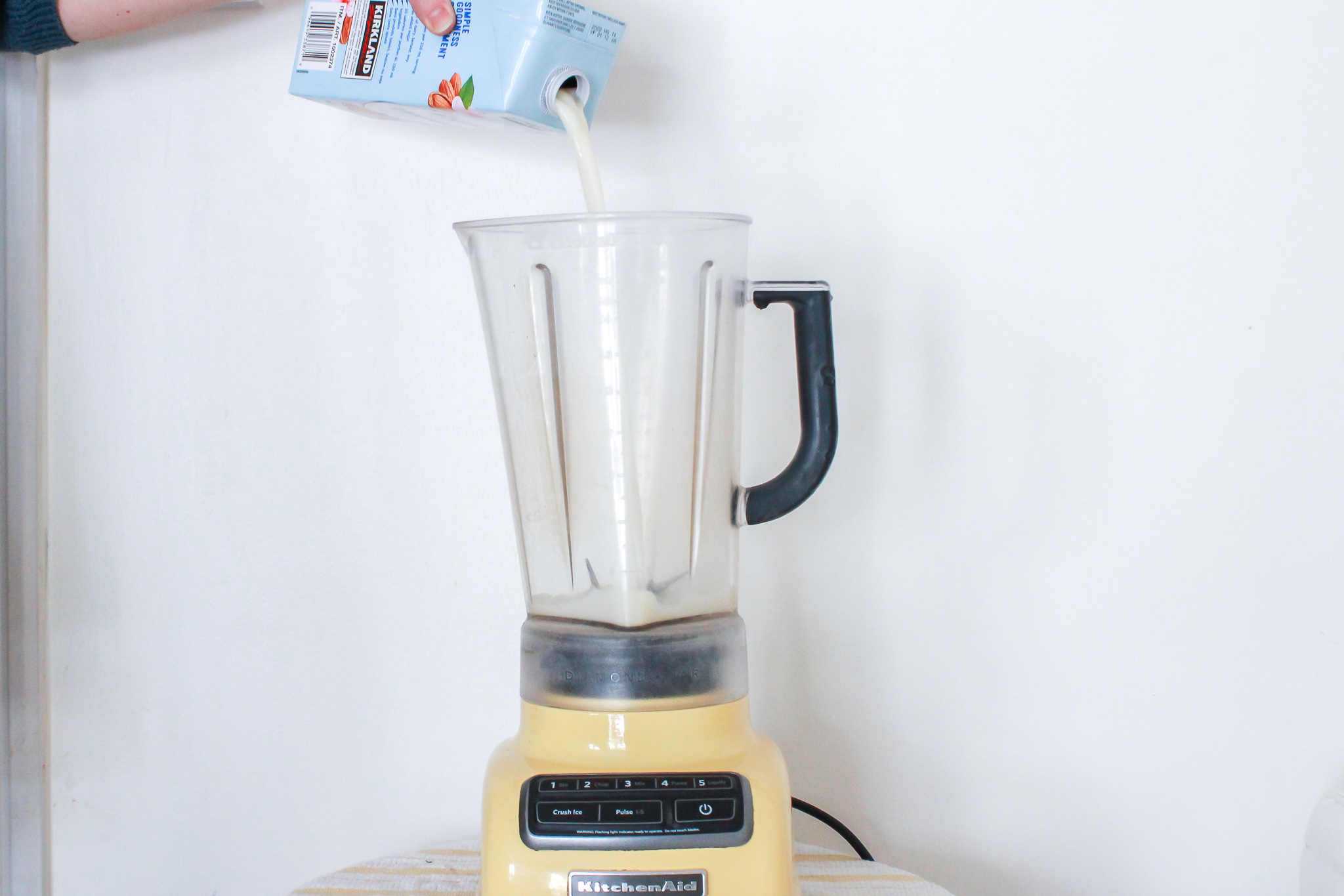 pouring almond milk into a blender
