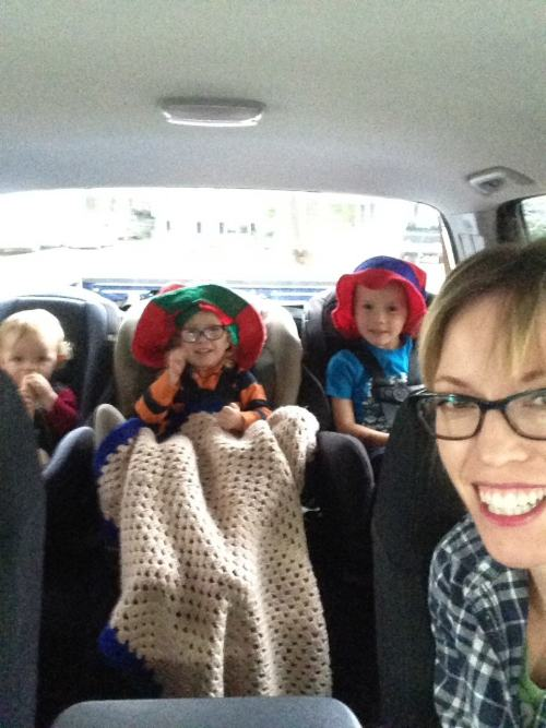mom in drivers seat and three toddlers in the back seat