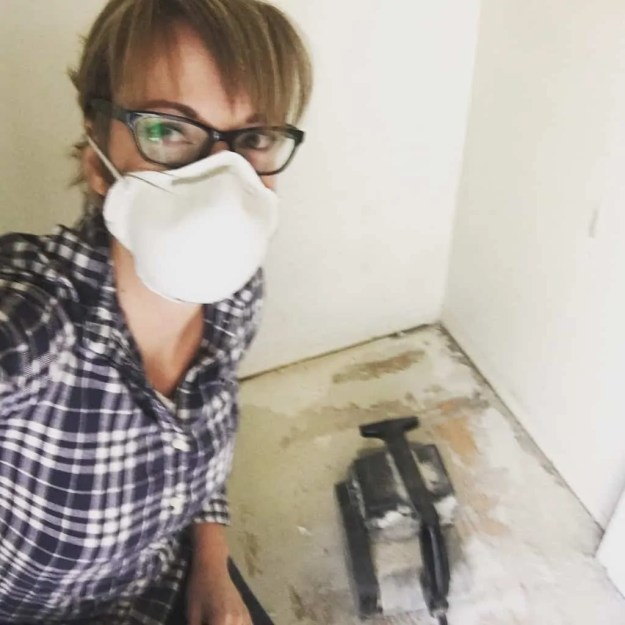 wearing dust mask and sanding the floor woman