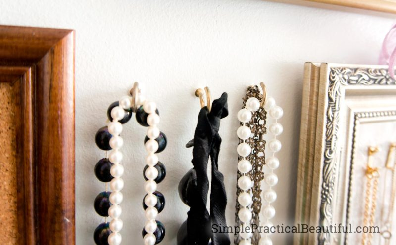 hooks in the wall hold large necklaces