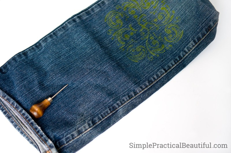 Use an awl to make a hold for the clasp screw post in the denim purse