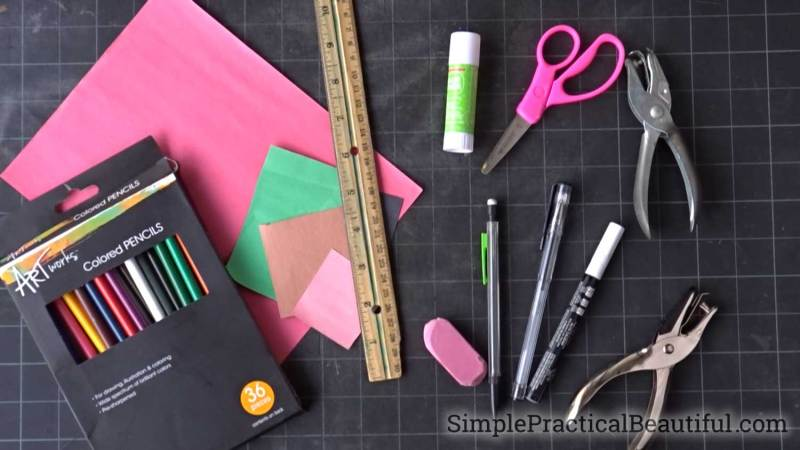 The supplies needed to make paper fruit characters, including a hole punch, colored pencils, and a glue stick