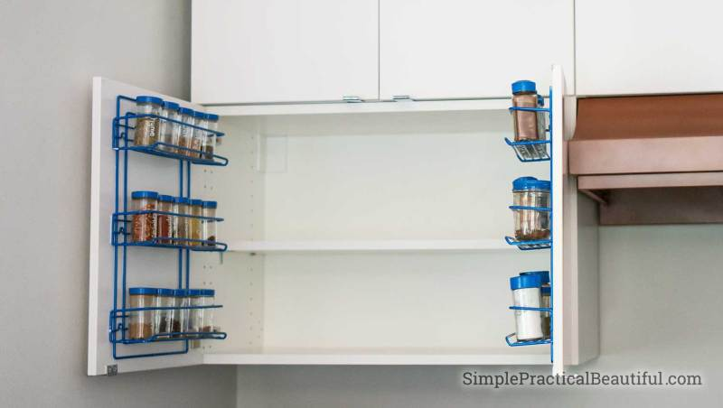 Spice racks mounted on the inside of a kitchen cabinet