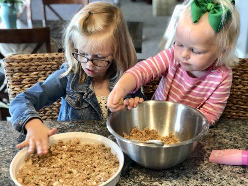 two girls making rhubarb crisp and putting pecan crumble on top