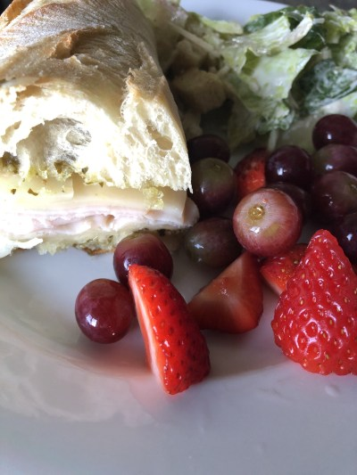 turkey pesto sandwich with fruit and salad
