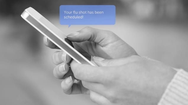 "Grayscale photo of hands holding a phone, with a blue text bubble floating above: ""Your flu shot has been scheduled!"""