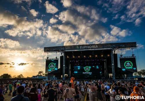 Outdoor Euphoria Fest stage at dusk with clouds in the sky and crowds of people