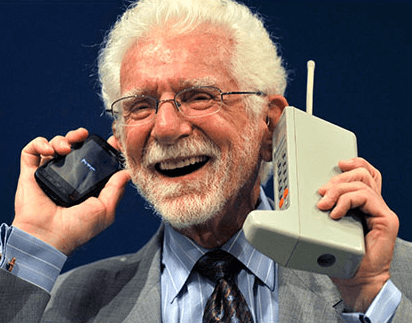 Man with white hair and beard dressed in a suit and tie, and holding a Motorola DynaTAC in his left hand and a modern cellphone in his right
