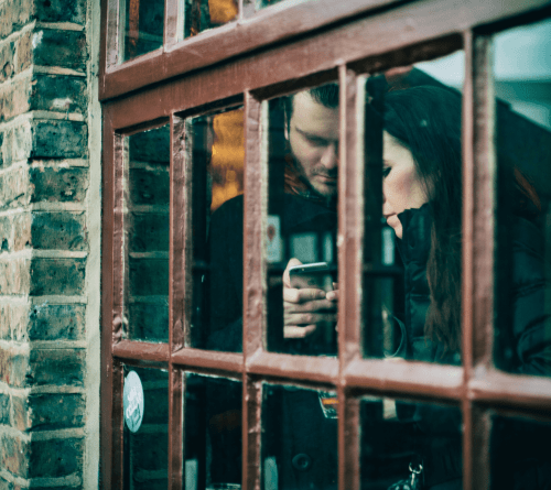 A man and woman holding phones, viewed at an angle through a window with panes