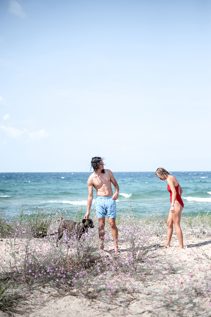 effects of grounding on inflammation - girl in swim trunks and girl in a red bathing suit at a beach that's on the great lakes with a brindle pitbull dog