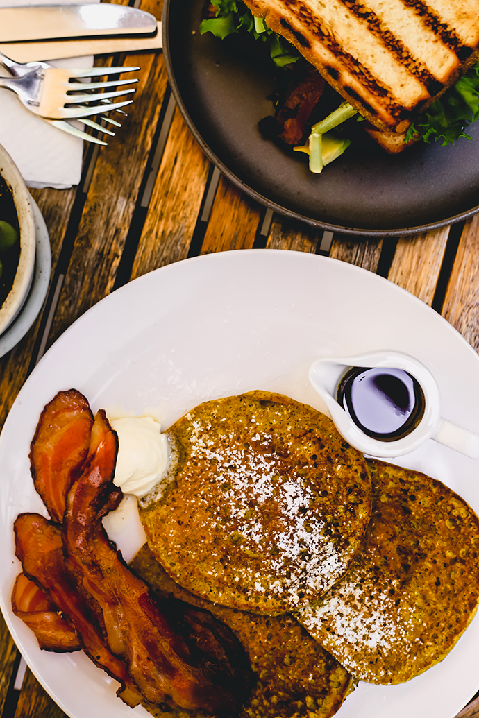 Golden turmeric pancakes with a ball of butter, red bacon on a white plate with a carafe for syrup.