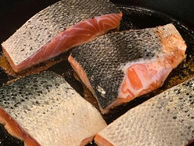 salmon being seared in pan