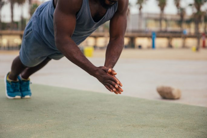 A man doing clapping push-ups outdoor