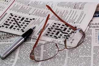An eyeglass and a pen on a newspaper crossword