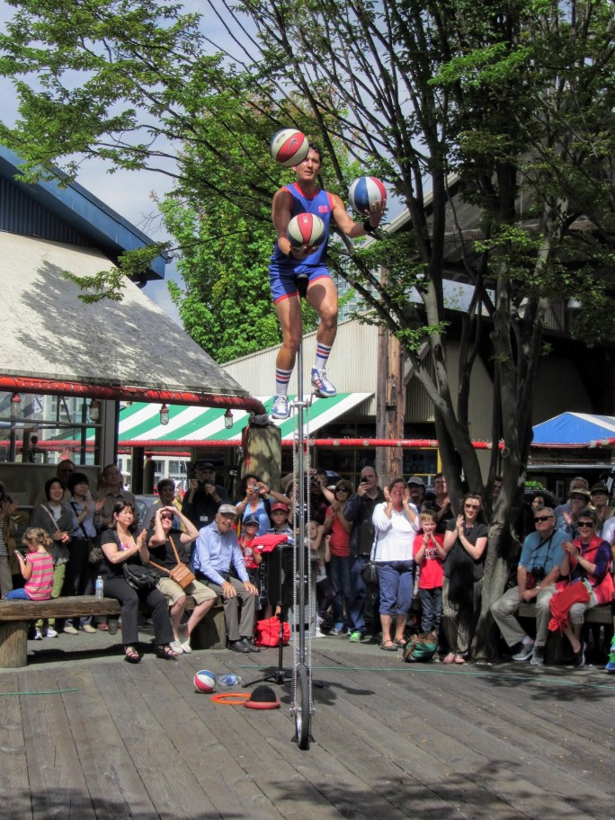 A man juggling basketballs while riding a tall unicycle