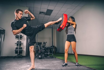 A man kicks a kick pad held by a woman at an indoor gym practice