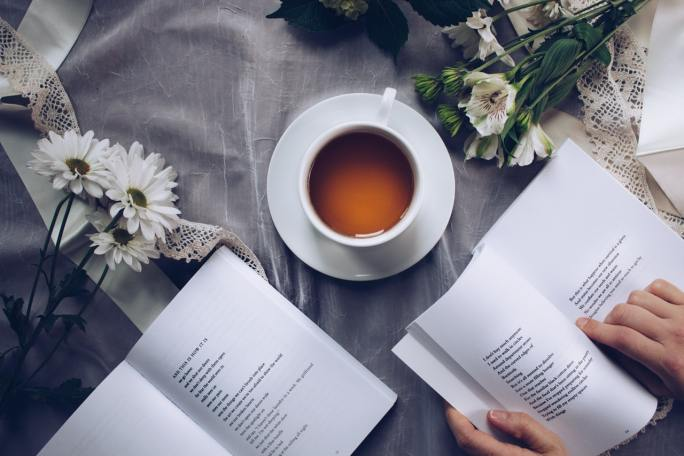 Two poetry book open on a table near a teacup, one is held by a hand