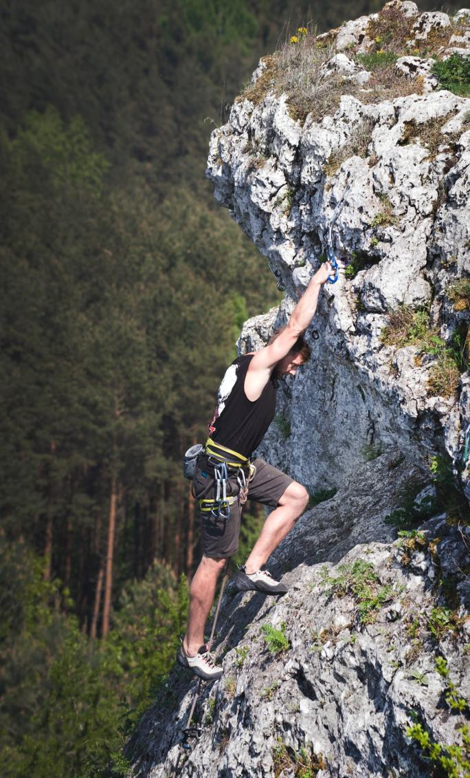 A man wearing a black tank top and brown shorts rock climbing