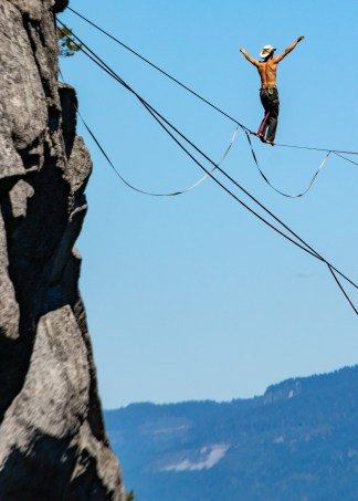 A man walking on a tightrope over a cliff