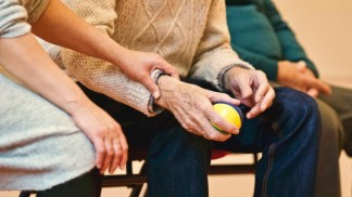 An elderly person sitting with a ball in his hand, while a younger person holds his hand