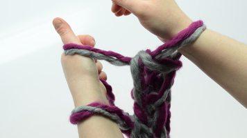Für die letzte Masche den Arbeitsfaden in die linke Hand nehmen und wie zuvor die Masche abstricken, um sie auf den rechten Arm zu legen.