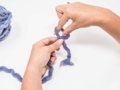 Die Stelle, an der sich die Fäden kreuzen, mit dem linken Daumen und Zeigefinger halten. Mit dem rechten Daumen und Zeigefinger in die Schlaufe greifen …