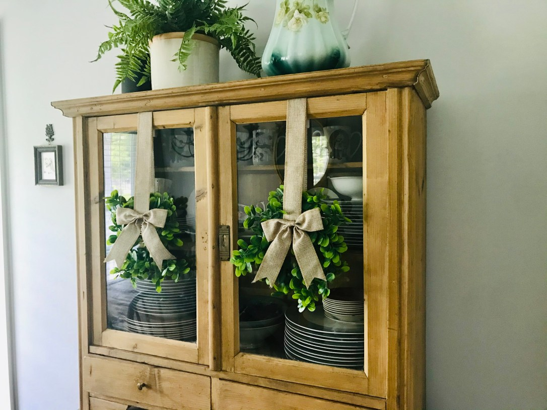 Antique wood china cabinet with faux green wreaths