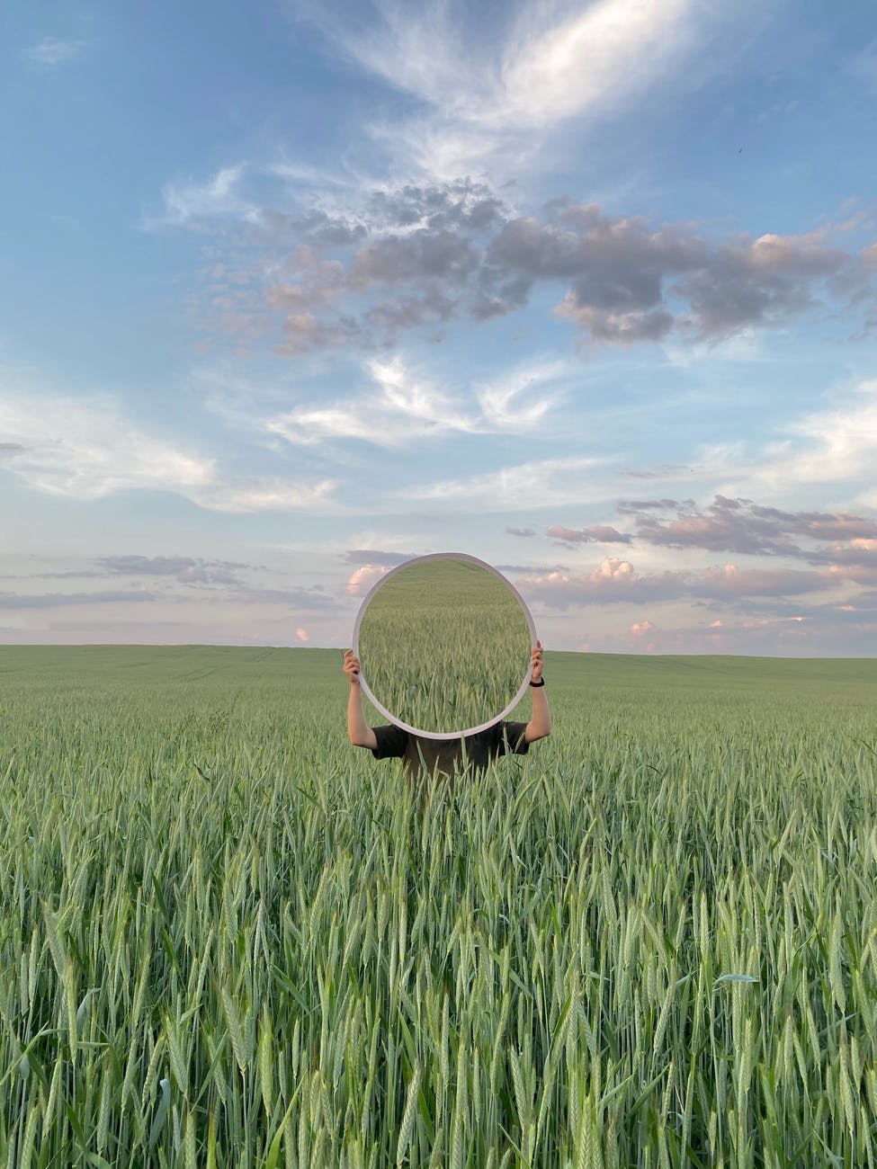 anonymous person in green grass with mirror