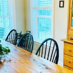 Farmhouse table with a real plant centerpiece and wood antique hutch with faux plant wreaths