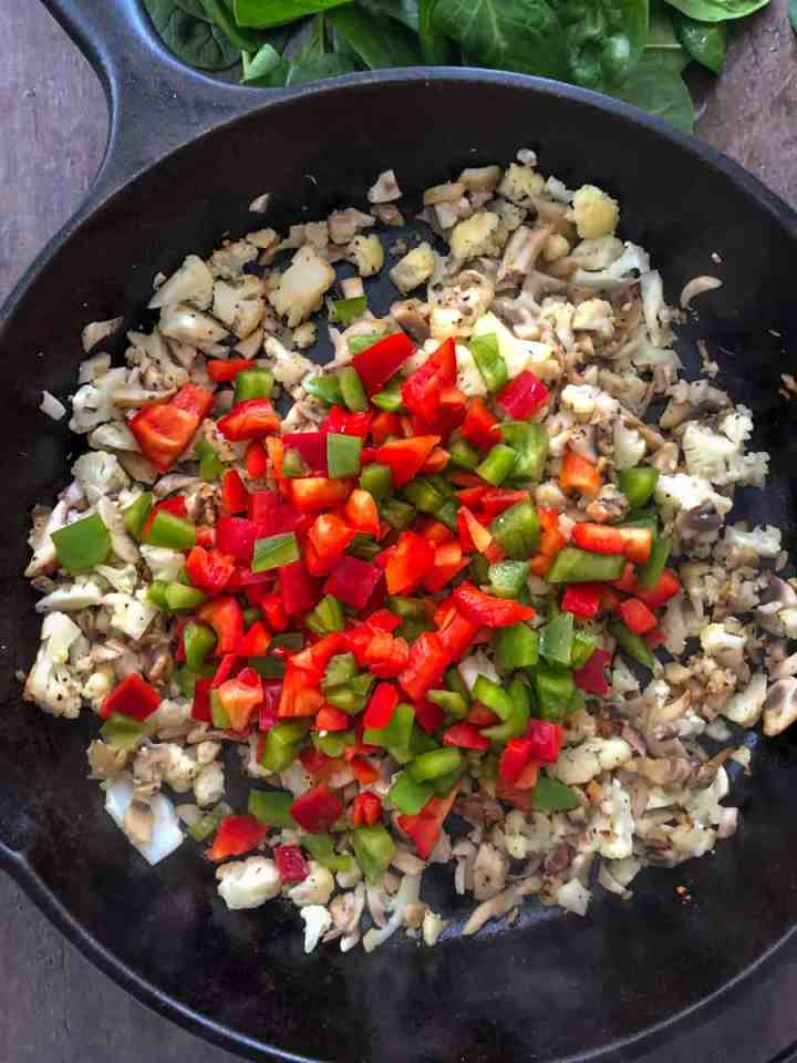 cauliflower-mushroom has in a skillet with red and green pepper chunks