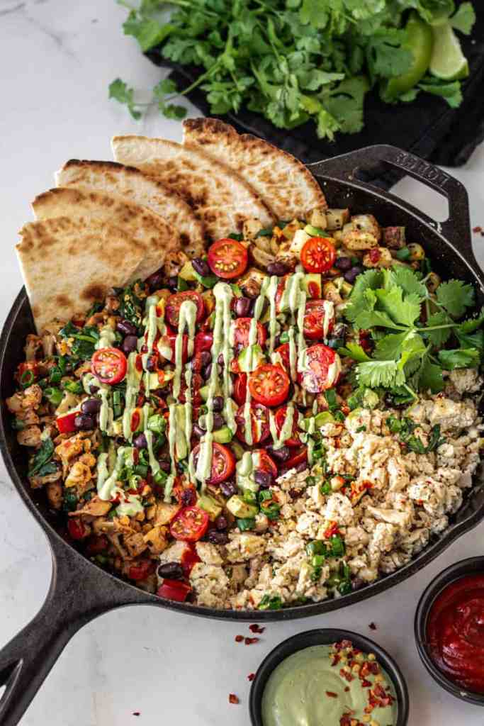 vegan breakfast hash in a skillet with tomato and avocado and cashew drizzles
