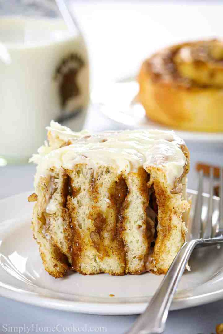 close up image of a sliced homemade cinnamon roll with cream cheese icing on top on a white plate