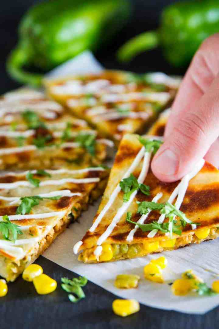 sliced chicken quesadilla with a corn, sour cream, and chopped cilantro on top