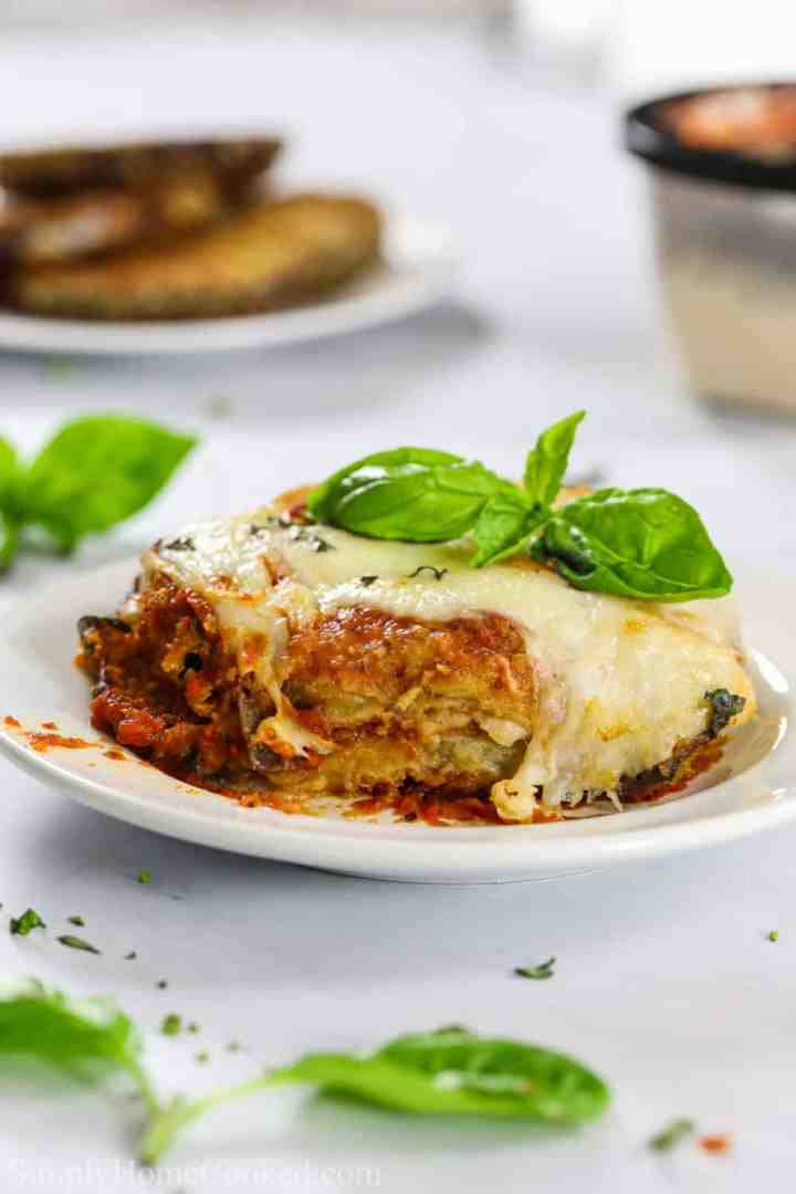 a piece of eggplant parmesan on a plate with some basil on top of the baked parmesan