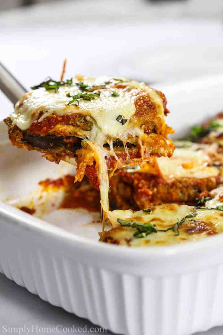 a spatula lifting a piece of eggplant parmesan over a casserole dish