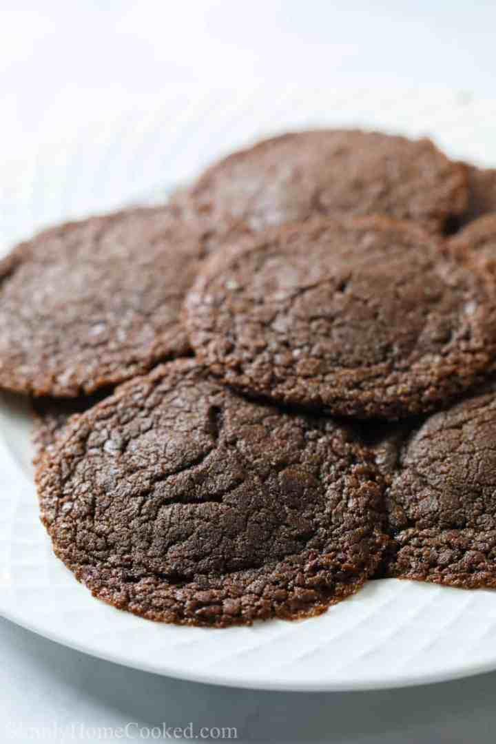 thin and chewy Nutella cookies stacked on top of each other on a white plate