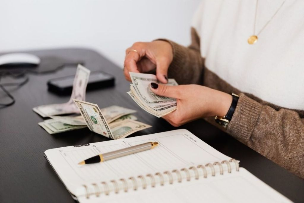Girl holding money with a college grocery list and budget