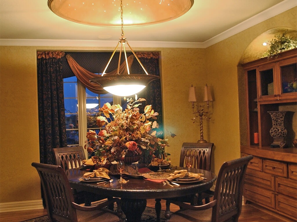 This is a dining room with a hanging light and floral arrangement.