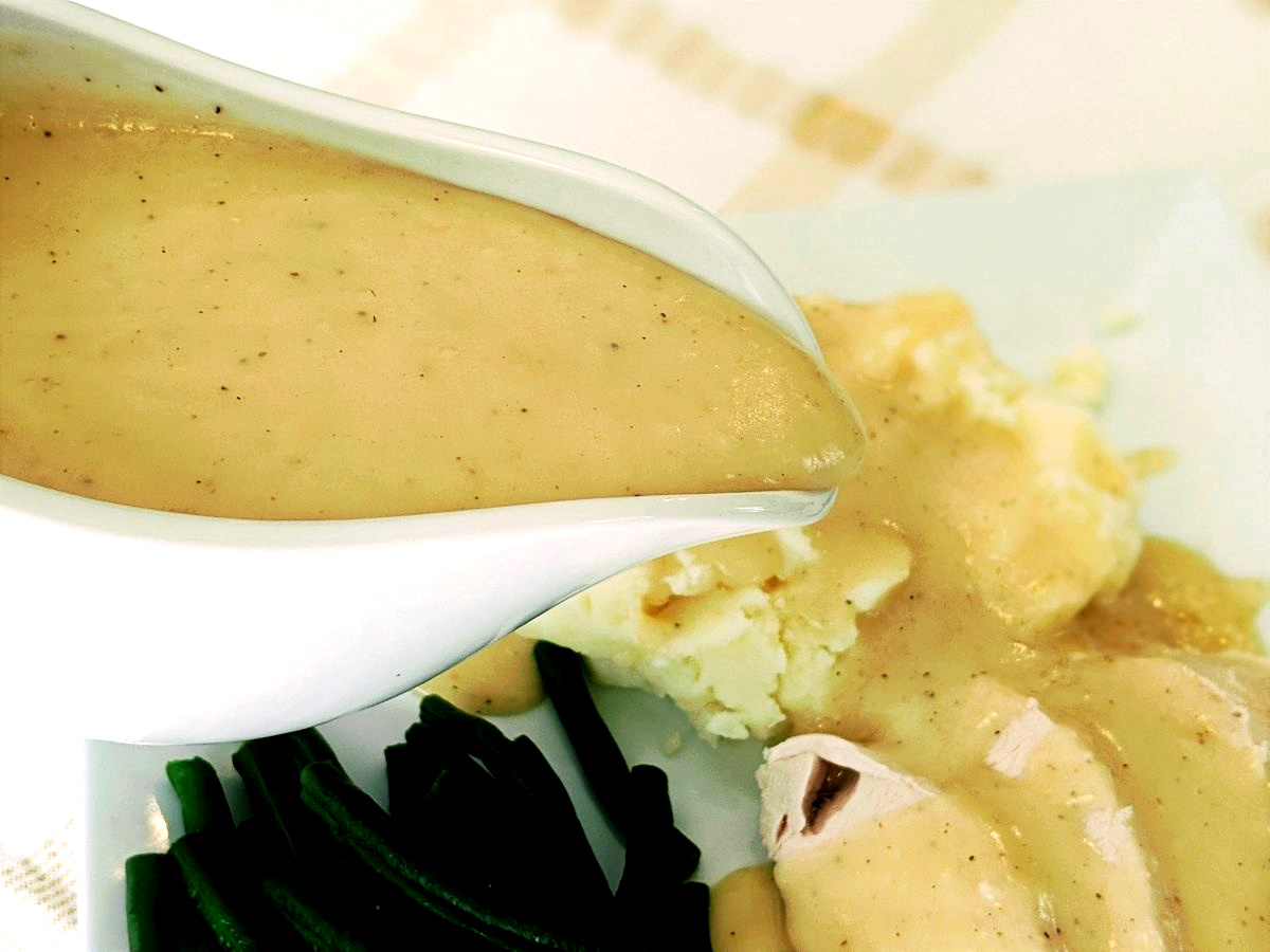 pouring turkey gravy over mashed potatoes