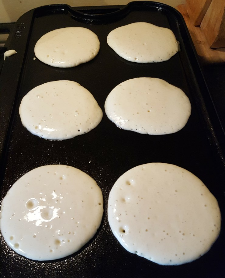 Six pancakes on a black cast iron griddle