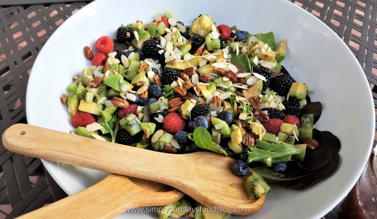 Bowl of the summer berry salad with wooden salad tongs outside on a table