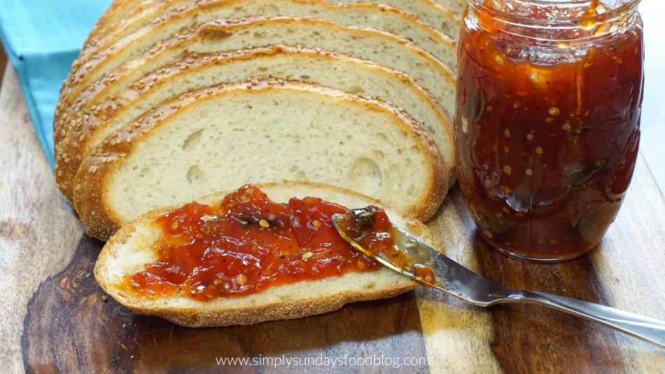 Spicy tomato jam spread on crusty bread and served on a cutting board next to a blue cloth