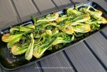 Sauteed baby bok choy served on a platter garnished with toasted sesame seeds