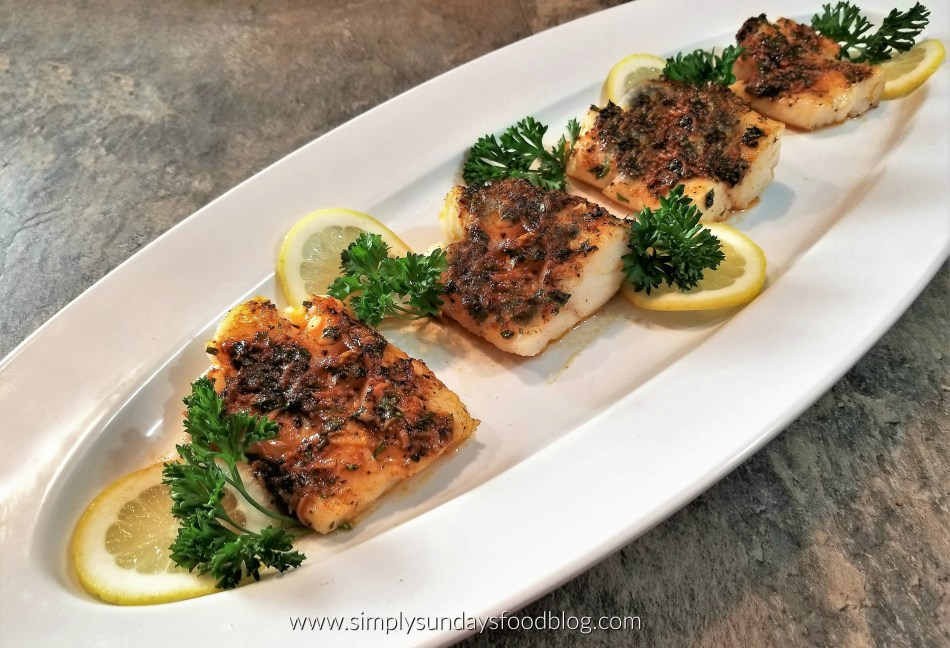 Broiled Cod fillets on a platter with fresh lemons and parsley