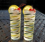 Two tall iced glasses with a refreshing vodka collins cocktail garnished with fresh lemon slices and maraschino cherries