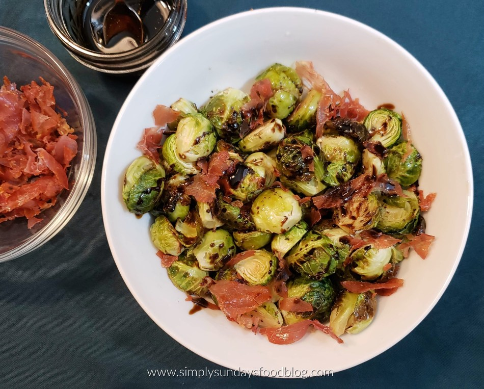 White bowl of caramelized brussel sprouts drizzled with a sweet maple balsamic glaze and topped with crispy, salty prosciutto