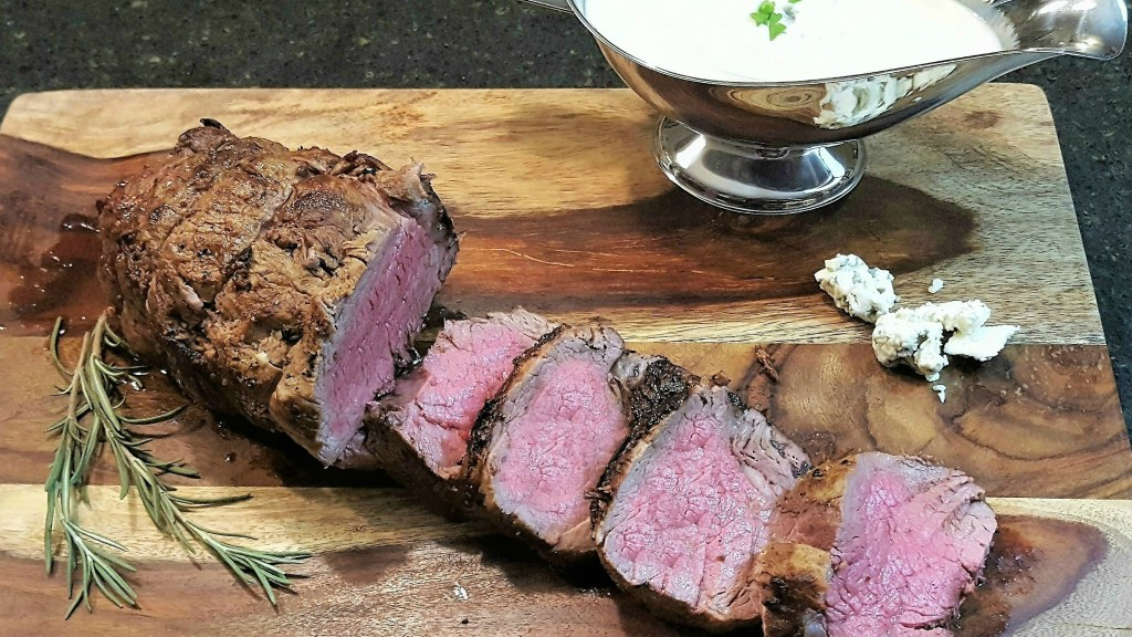 Roast fillet of beef sliced on a wood cutting board. The center of the beef is a pink medium, there is fresh rosemary on the board and a silver gravy boat filled with a white creamy gorganzola cheese sauce
