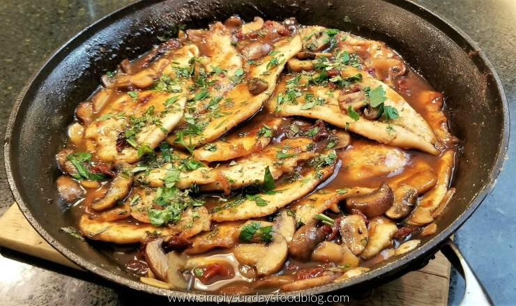A saute pan filled withthinly slice browned chicken cutlets, rich brown marsala wine sauce, porto bella mushrooms, red sundried tomatoes, white sauteed garlic and fresh green chopped parsley and basil leaves